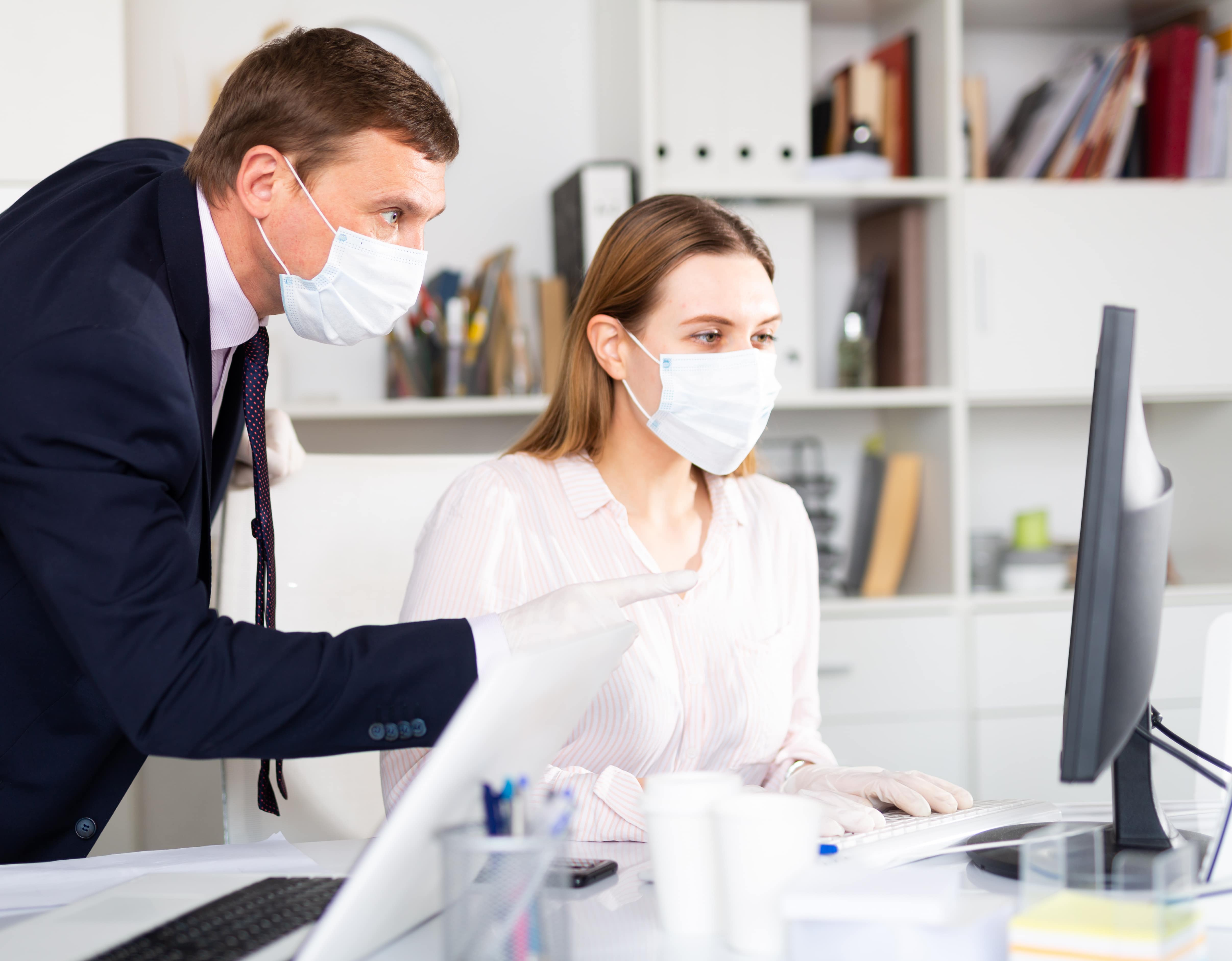 Man helping his colleague to prepare document on your computer